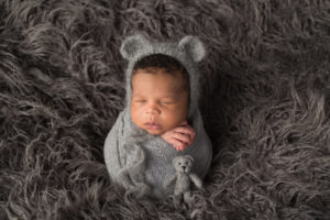 Dallas newborn photographer poses baby with bear hat and tiny teddy bear to match