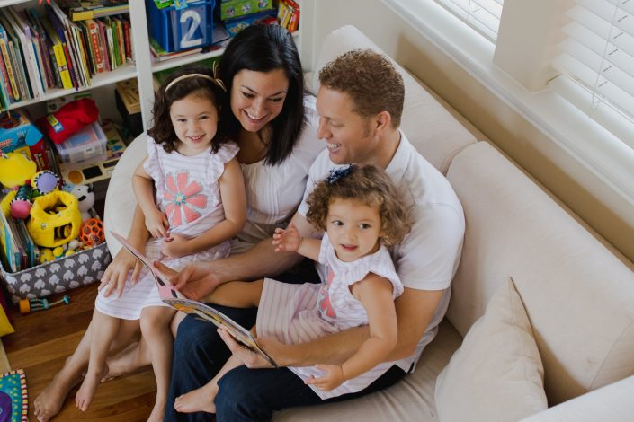 Family reading a book together on their couch