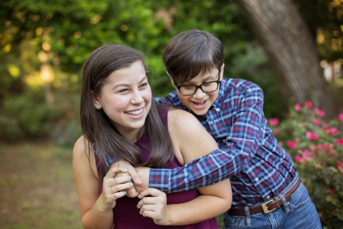 Brother and sister hugging in Prairie Creek Park in Richardson Texas