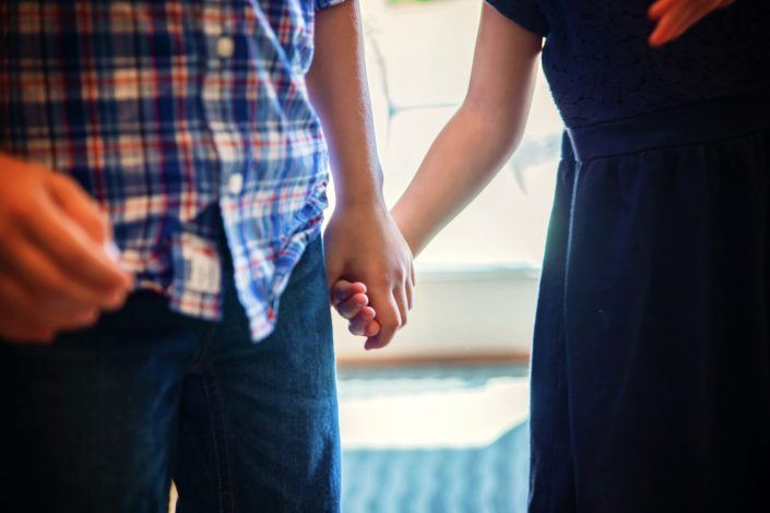 Brother and sister holding hands during family photo shoot