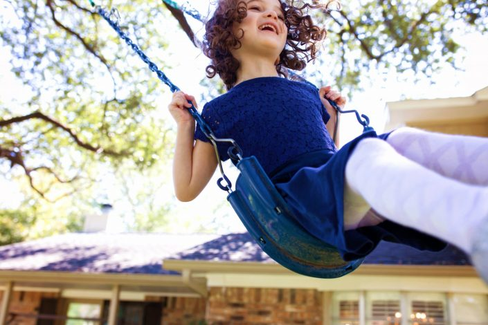 Little girl on swing outside her house during family photo session