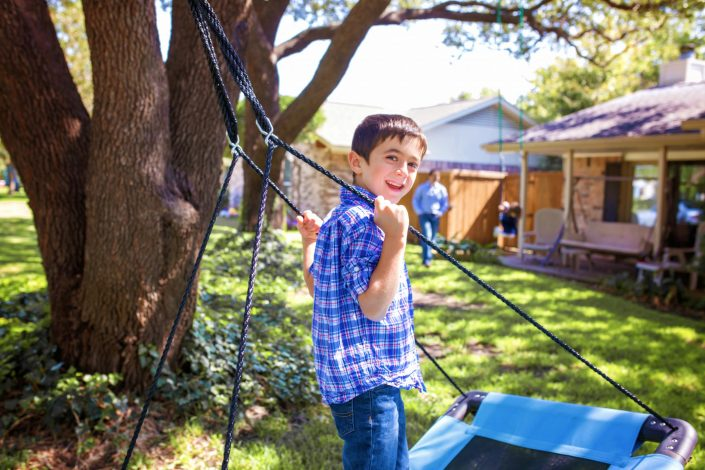 Little boy on a swing outside his house during lifestyle family photo shoot
