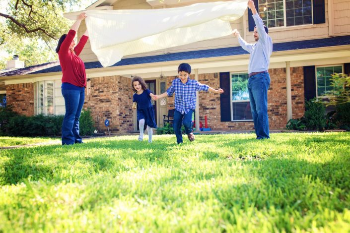 Family playing parachute game outside home during photo session