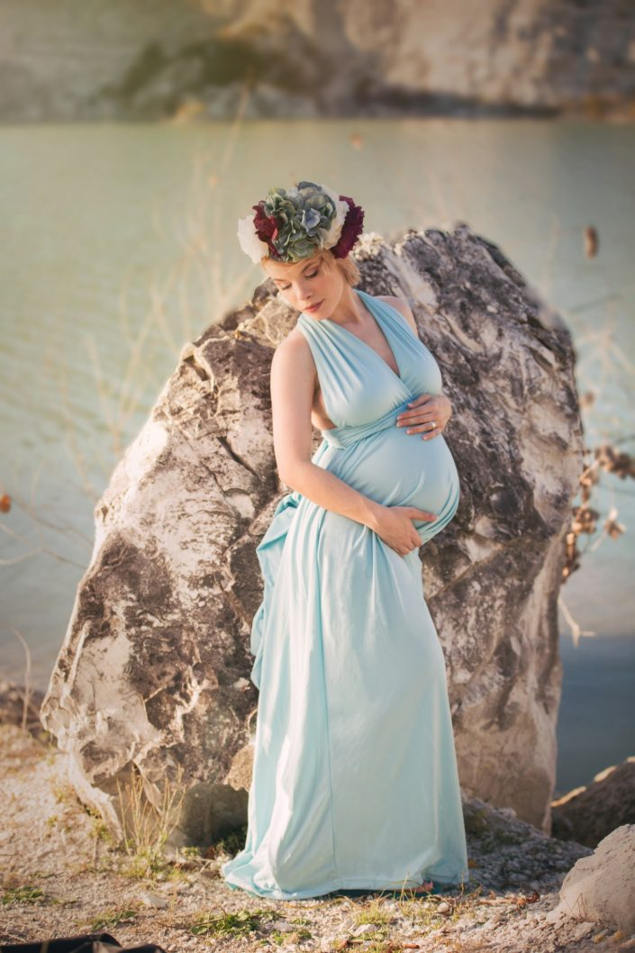 Dallas mother to be in styled maternity shoot posed in front of large boulder by a lake wearing light blue dress and floral crown