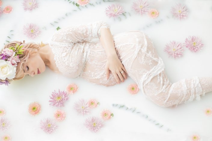 Dallas mother to be photographed in white lace dress in milk bath surrounded by light purple and pink flowers with floral crown