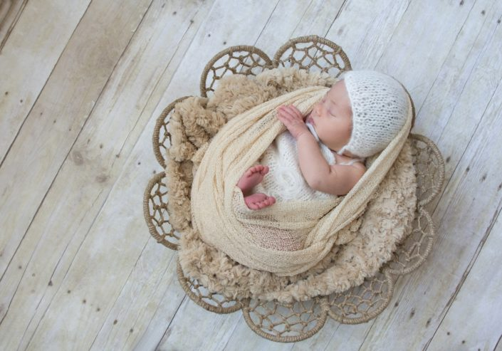 baby girl in dream catcher bowl in ivory colored mohair jumper, with cream wrap