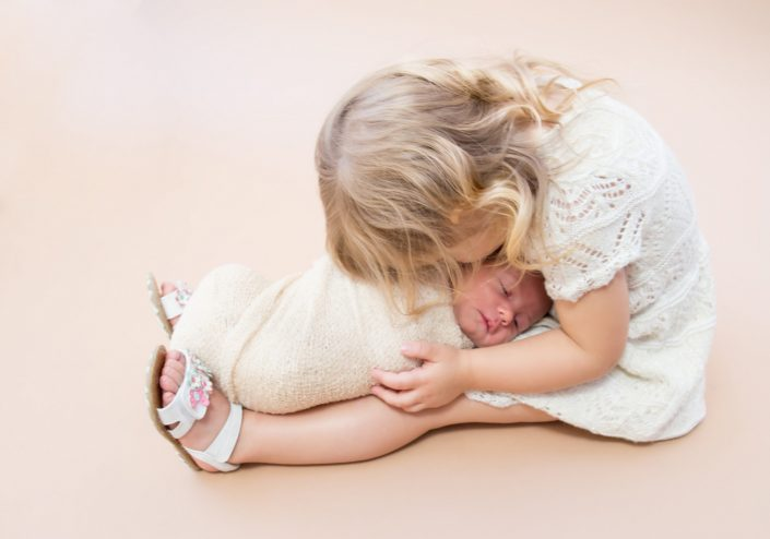Little girl from Dallas holding her newborn baby sister