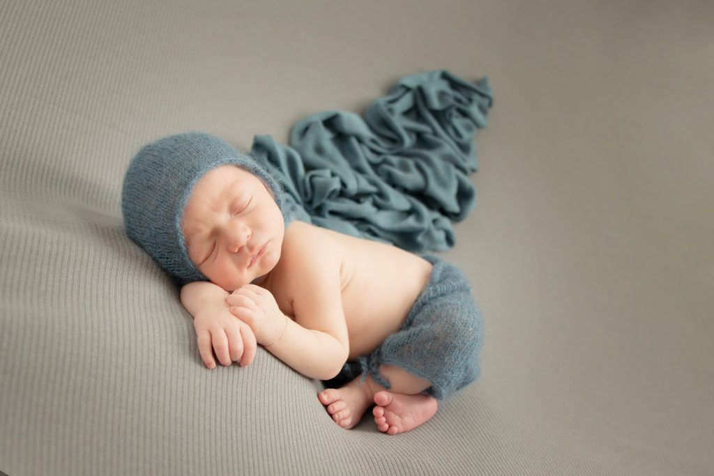 Dallas newborn photographer photographs baby boy in blue outfit on a grey background