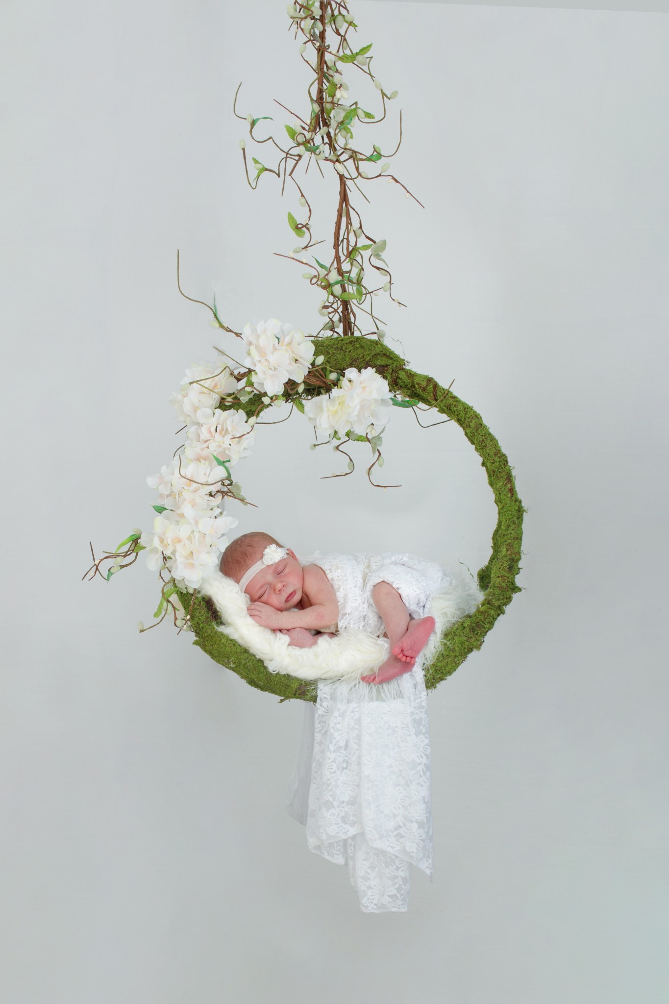Composite newborn image of baby in floral and moss swing on a white background.