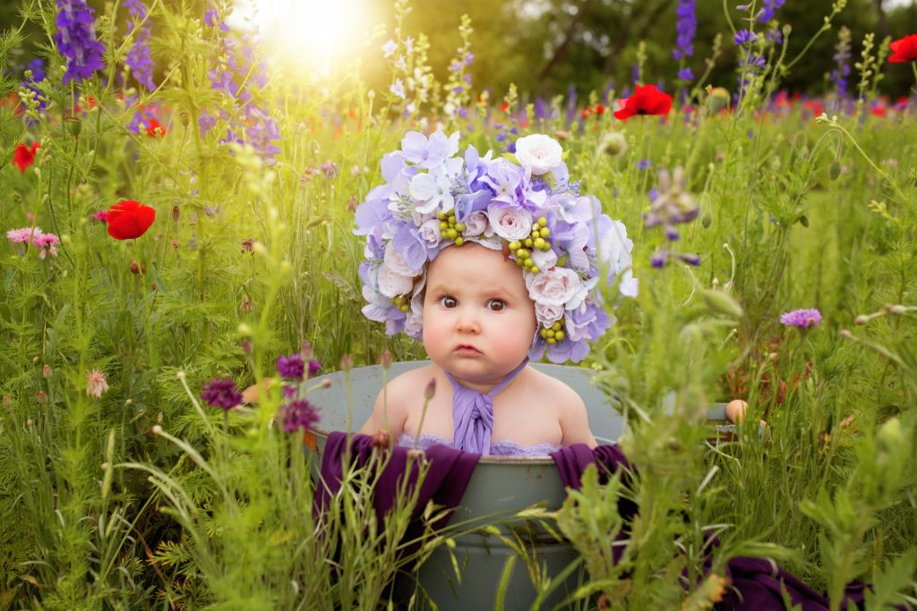 Dallas Baby Photographer photographs baby in floral bonnet in Richardson Texas wildflower field