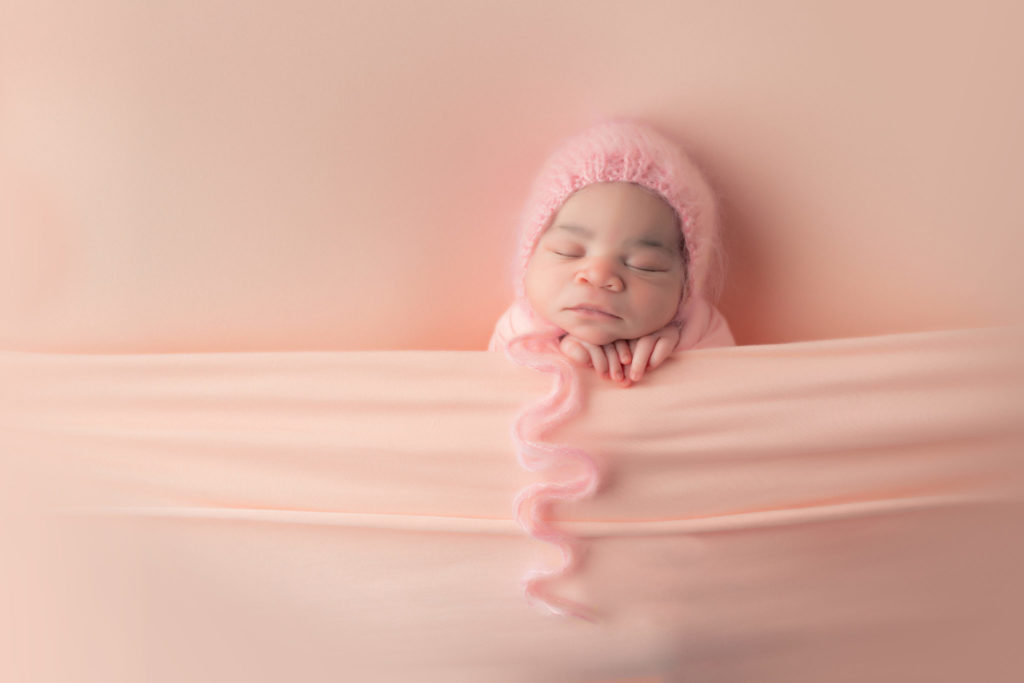 newborn girl picture all pink tucked in