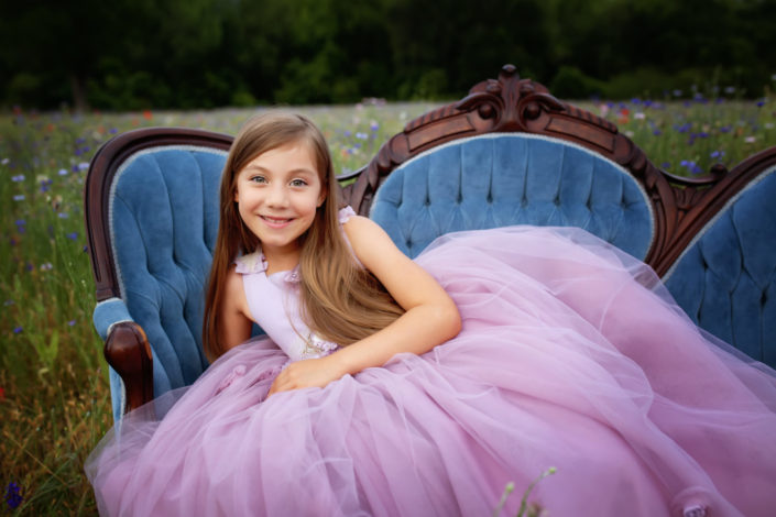 Fairy tale child photography session in wildflower field at Crowley Park in Richardson Texas girl wearing beautiful dress on antique couch