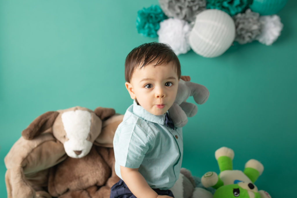 Dallas baby photographer designs baby first birthday session with teal backdrop and stuffed animals