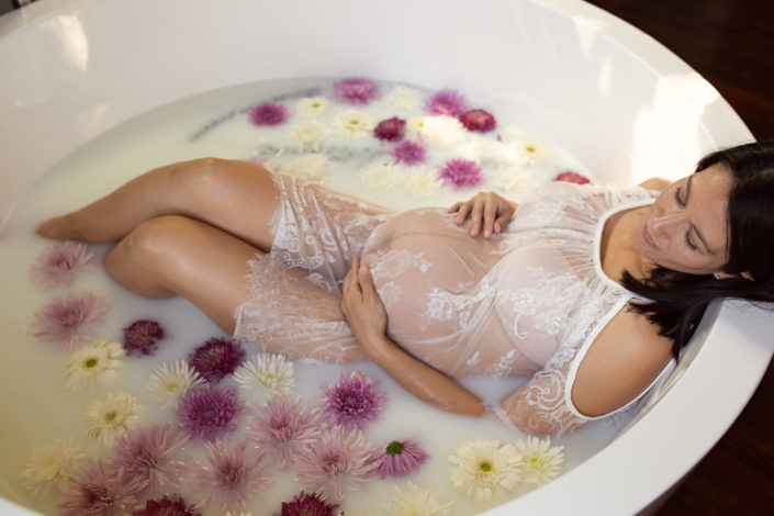 Pregnant mother in milk bath wearing lace dress surrounded by flowers at Origins Birth Dallas Swiss Ave downtown