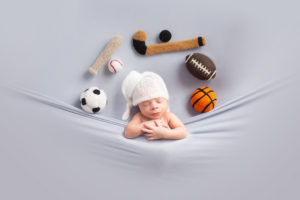 Dallas newborn photographer poses baby in tucked in pose with all sports balls and objects