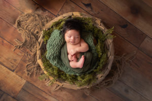 Dallas newborn photographer poses baby in large bowl with green and brown accents