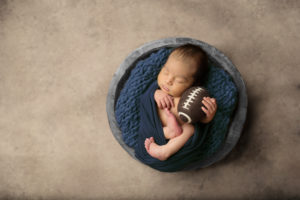 Dallas newborn photographer poses baby in bowl with football and cowboys colors
