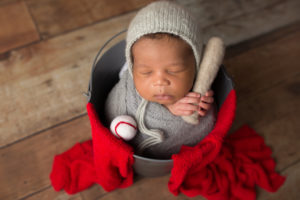 dallas newborn photographer poses baby in bucket with bat and ball