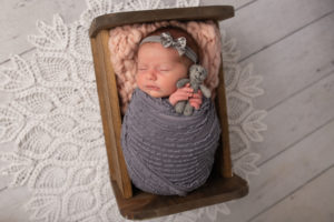 dallas newborn photographer poses baby girl in sweet little bed holding tiny teddy bear